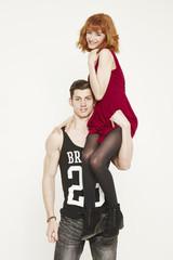 Muscular young man lifting young woman