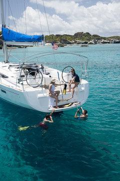 People swimming near yacht