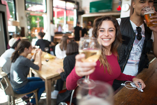 Young woman making celebratory toast in bar
