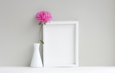white frame, empty mock-up, beside vase with pink aster