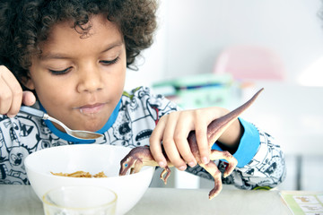 Boy eating cereal with toy dinosaur