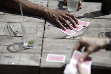 Hands of young men playing cards