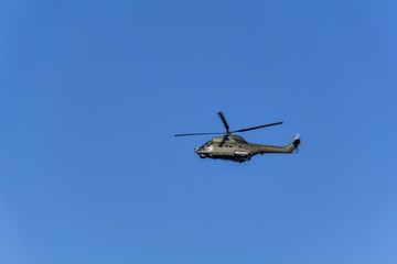 The military helicopter against the blue sky. Rotary wing aircraft, flying in the sky.