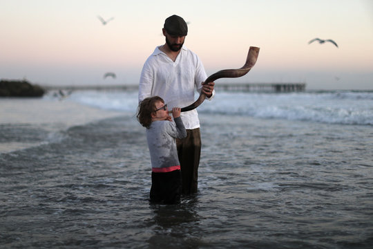 Levitch holds a shofar for his daughter to blow at a Tashlich ceremony during the Nashuva Spiritual Community Jewish New Year celebration on Venice Beach in Los Angeles