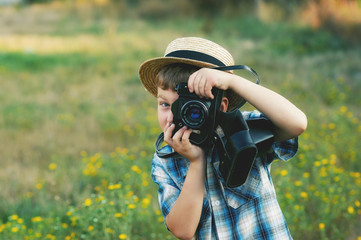 A little boy with an old camera .Young cheerful photographer
