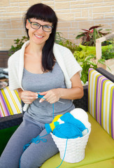 A smiling young woman knits the knitted socks with colored woolen yarn.