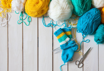 A woman knits knit socks with children's knitting needles. Stripes of turquoise, yellow and white colors.