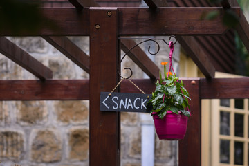 Snack sign and flowers in garden