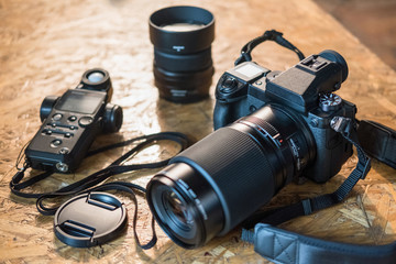 photo equipment and camera on a wooden table close-up. modern digital camera