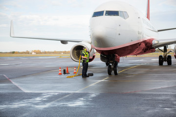Worker Charging Airplane On Wet Airport Runway