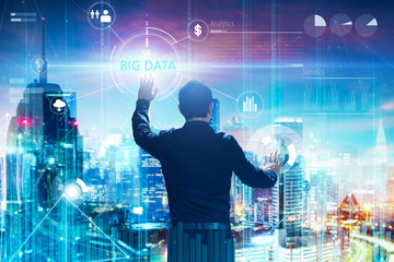 """Back view of a businessman touching """"BIG DATA"""" word on digital virtual screen with both hands. Hi-tech business concept ."""