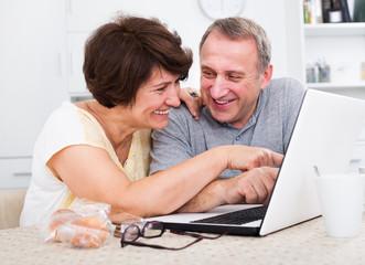 Mature man and woman looking at laptop
