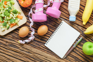 Healthy eating, dieting, slimming and weight loss concept - Top view of green apple, bananas, measuring tape, dumbbells, blank note book and vegetables on wooden background. copy space for Text