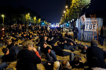 French farmers sit on hay as they stage a demonstration on the Champs-Elysee avenue in Paris