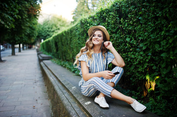 Portrait of a stunning young woman in striped overall sitting in the park and listening to the music with her earphones on.