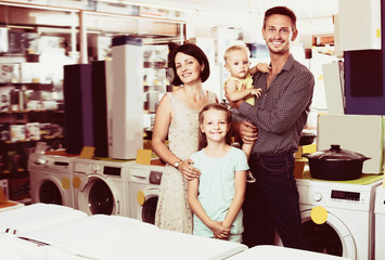 Glad young family with two children shopping