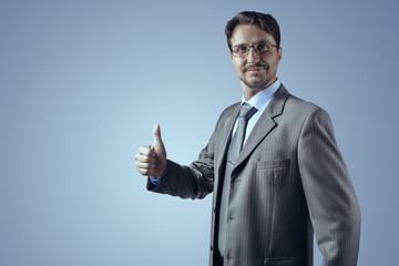 Businessman in gray suit smiling and thumb up