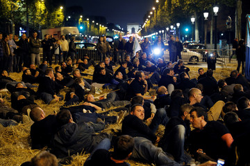 French farmers sit on hay as they stage a demonstration on the Champs-Elysees avenue in Paris
