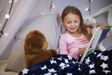 Girl watching a picture book with a teddy bear .
