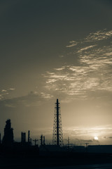 Silhouette oil refinery at sunrise. Oil factory, petrochemical plant tower, gas flare, smoke stacks and machinery in Corpus Christi, Texas, USA. Petroleum industry background. Vintage tone.