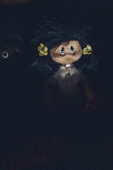 Possessed dolls emerge from darkness. Halloween nightmare. Original photo of ancient rag doll (copyrights free) retouched and coloured, neither artworks, layers nor any references were used