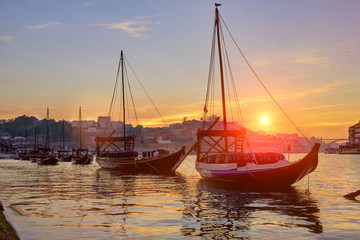Porto old town skyline on the Douro River with rabelo boats at sunset