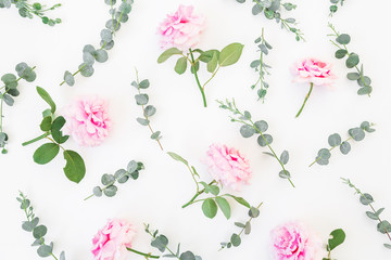 Floral pattern of pink flowers and eucalyptus branches on white background. Flat lay, top view. Valentine's background