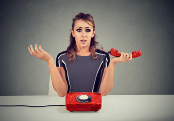 Shocked young woman receiving bad news on the phone