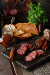 Various varieties of sausage on a cutting vintage board, fresh bread baguette, dried tomatoes, fresh green basil and beer on a rustic wooden gray background. Close up