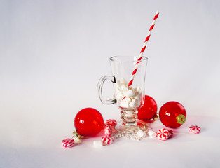 Christmas decoration on white background. Red balls ornaments and candy. Cup with marshmallow and striped paper straw