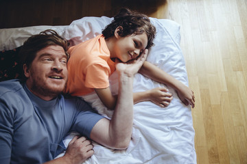Father and son relaxing on bed
