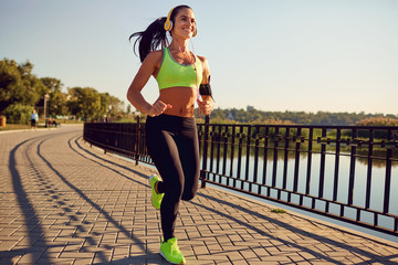A sports girl in headphones runs through the park. Healthy lifestyle.