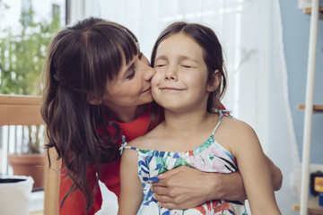Mother kissing cheek of daughter