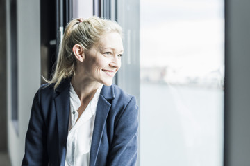 Smiling businesswoman looking out of window