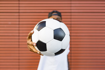 Man's hand holding soccer, close-up