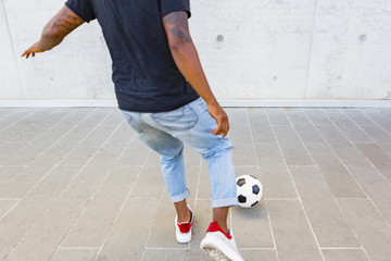 Back view of young man playing with a soccer ball against concrete wall, partial view