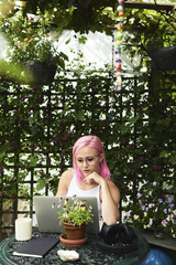 Charming lady with pink hair working on laptop in garden.