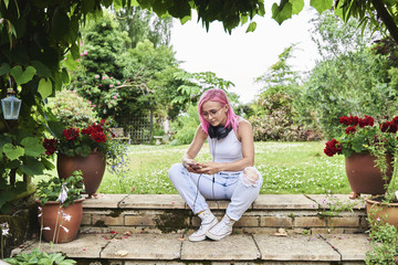 Hipster girl with pink hair browsing mobile phone in garden.