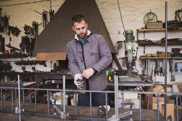 A blacksmith is putting on his safety gloves and workgear before working on a piece of metal in a workshop.