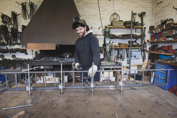 A smiling blacksmith wears safety gear and is about to weld a metal construction in a metalsmith's workshop.
