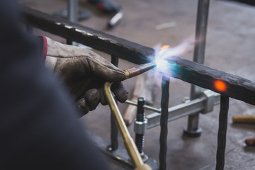 A blacksmith in a leather apron is using a cutting torch in his workshop.