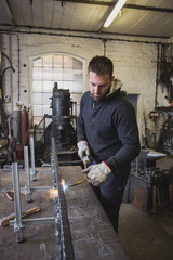 A blacksmith is using a cutting torch in his workshop.