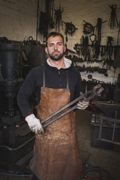 A blacksmith in a leather apron carries a tong and is portrayed in his workshop.