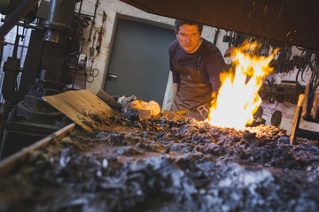 A blacksmith heating up an iron bar in a workshop