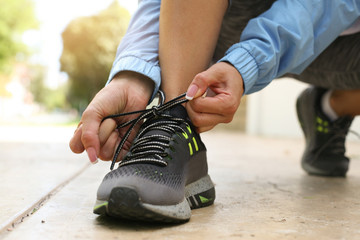 Sportswoman tying shoelaces. Sportswoman tying her shoelaces before the training. Close up.