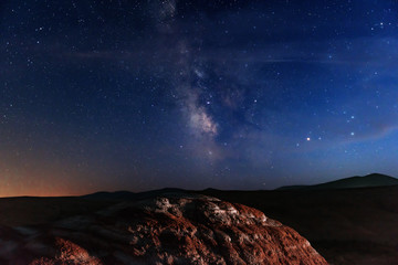 Milky way on starry sky over red mountains