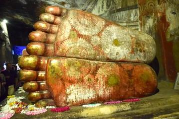 Füsse einer Buddastatue mit aufgemalten Blumen