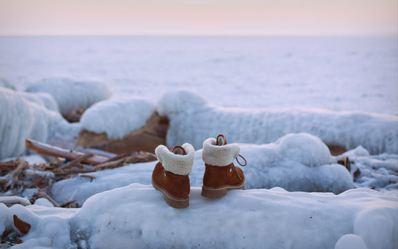 the shoes on the background of the frozen sea at sunset