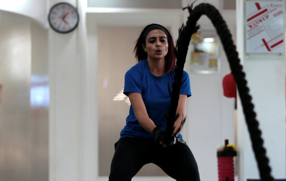 A woman swings a rope during cross fit training at a gym in Islamabad