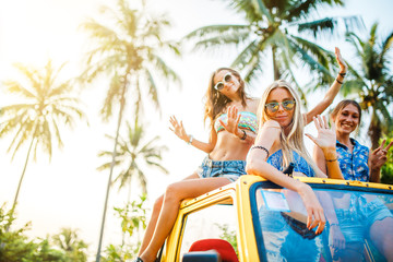 group of three russian girls vacationing in thailand atop offroad truck waving